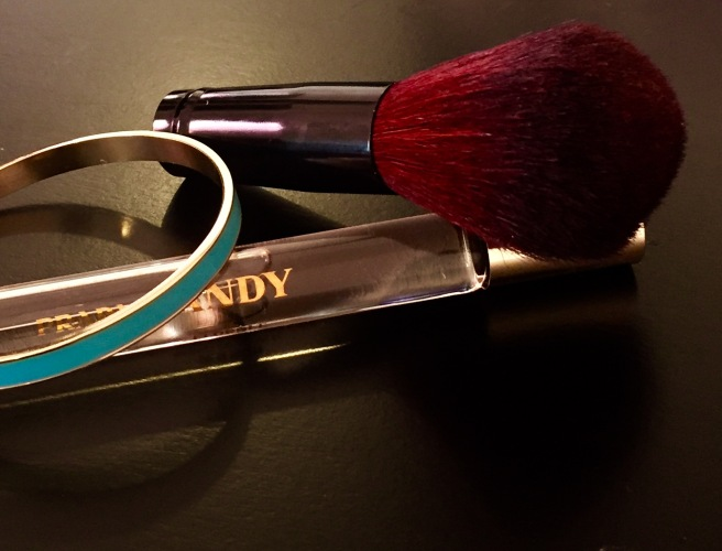Blush brush, Prada Candy roll on perfume, gold and teal bangle. Photo by Mara Lucas