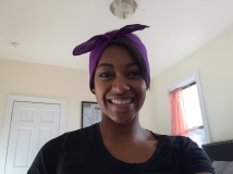 Square purple headscarf folded into rectangle and tied around head.