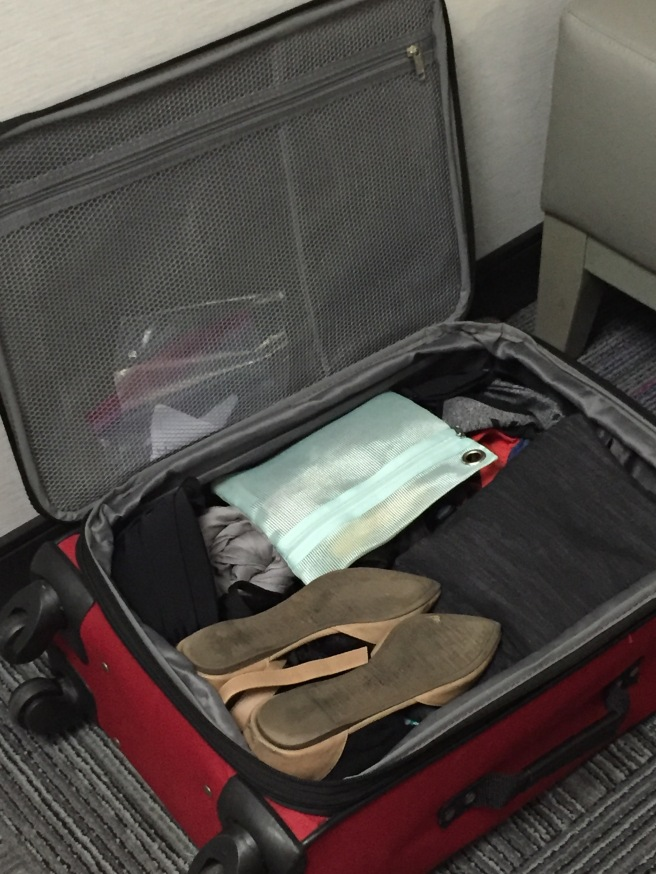 Packed red suitcase, ballet flats, make up kit. Photo by Mara Lucas.